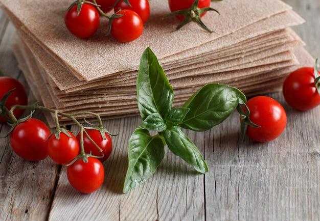 Folhas de lasanha crua e tomate cereja em uma mesa de madeira close-up