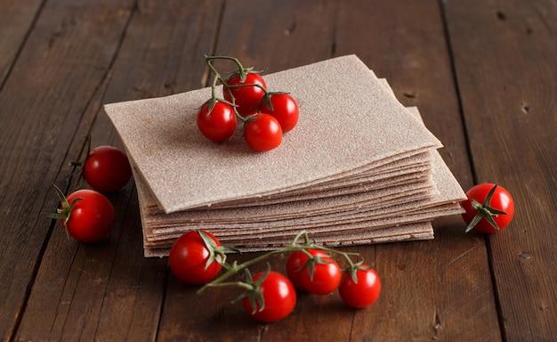 Folhas de lasanha crua e tomate cereja em uma mesa de madeira