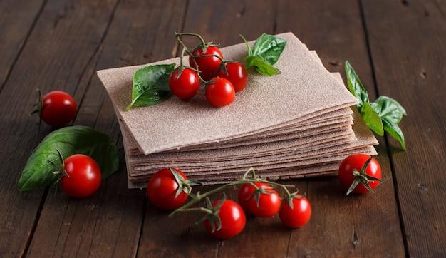 Folhas de lasanha crua, manjericão e tomate cereja em uma mesa de madeira fecham