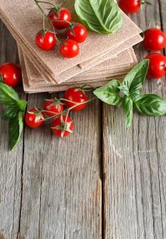 Folhas de lasanha crua, manjericão e tomate cereja em uma mesa de madeira