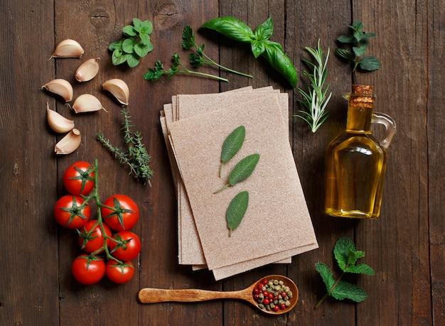 Folhas de lasanha de trigo integral, vegetais e ervas na mesa de madeira