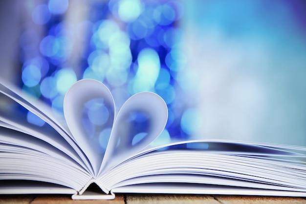 Folhas de livro curvadas em forma de coração na mesa de madeira contra luzes desfocadas