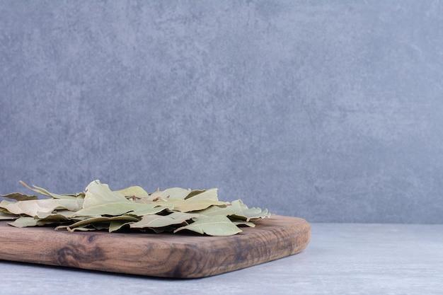 Folhas de louro verdes secas em uma bandeja de madeira. foto de alta qualidade