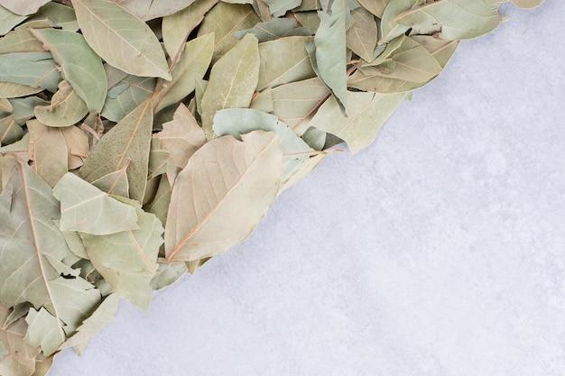 Folhas de louro verdes secas em uma bandeja no fundo de concreto. foto de alta qualidade