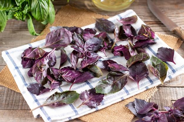 Folhas de manjericão fresco em um guardanapo sobre uma mesa de madeira. secagem das folhas antes de congelar. conceito de comida congelada