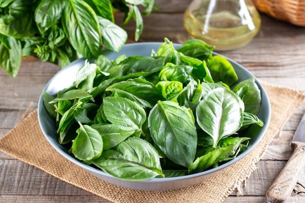 Folhas de manjericão fresco em uma placa de corte em uma mesa. conceito de alimentação saudável.