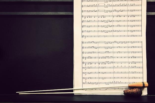 Folhas de música e bastões de maestro