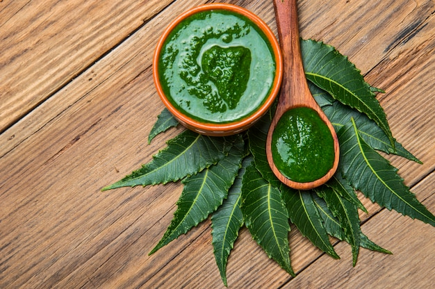 Folhas de neem medicinal com colar na mesa de madeira