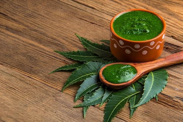 Folhas de neem medicinal com pasta em fundo de madeira