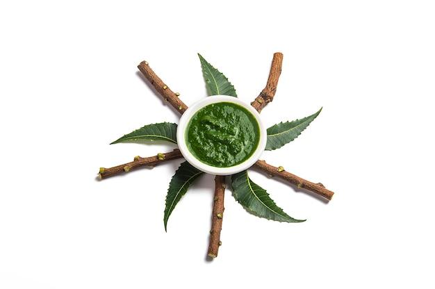 Folhas de neem medicinal com pasta na tigela e galhos no fundo branco