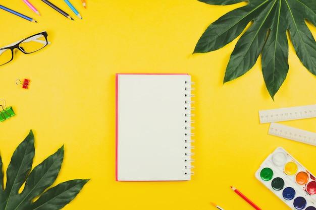 Folhas de negócios com folhas tropicais e acessórios comerciais e artísticos: lápis de cor, réguas, caderno, clipes, aquarelas etc.