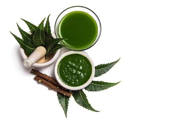 Folhas de nim medicinal em almofariz e pilão com pasta de nim, suco e galhos na superfície branca