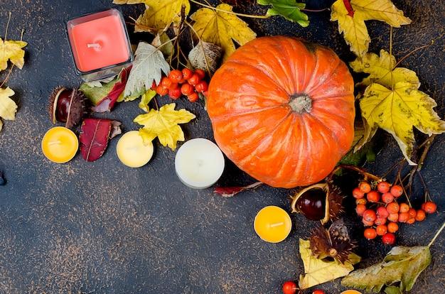 Folhas de outono, abóbora, castanhas, velas em um fundo escuro