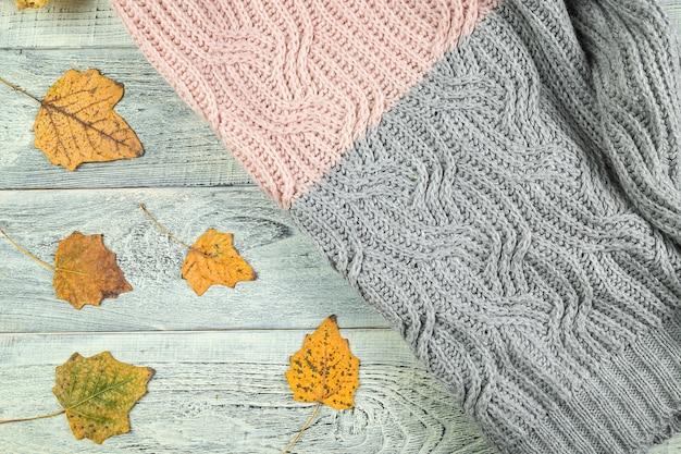 Folhas de outono amarelas sobre um fundo de madeira texturizado velho com uma jaqueta texturizada
