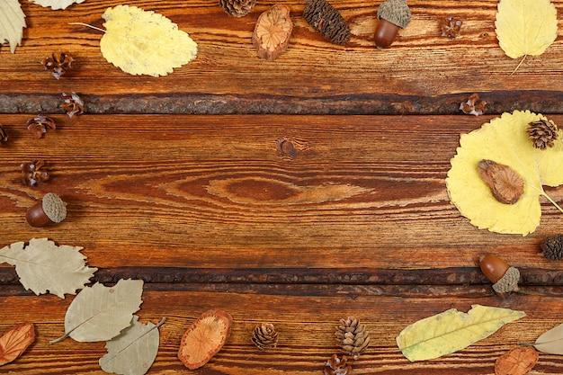 Folhas de outono amarelas sobre um fundo escuro de madeira velho, com um espaço em branco para texto
