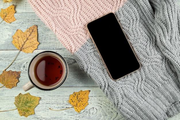 Folhas de outono amarelas, uma xícara de chá e um smartphone em um fundo de madeira velho