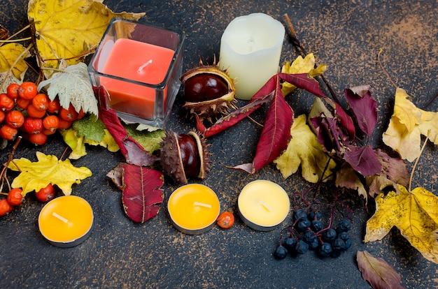 Folhas de outono, castanhas, velas em um fundo escuro