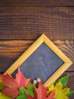 Folhas de outono coloridas com moldura de madeira para texto em um texturizado de madeira