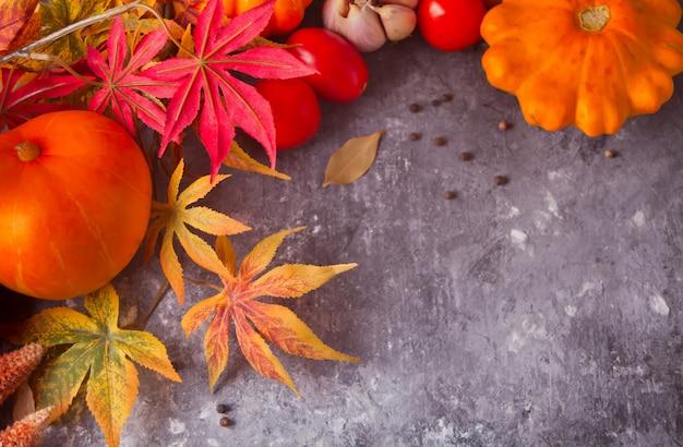 Folhas de outono com abóboras e tomates no fundo de concreto