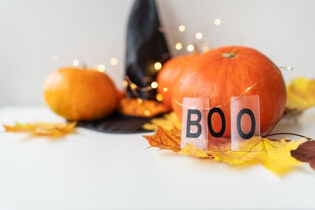 Folhas de outono com borda de abóbora na parte inferior, chapéu preto, fundo lindo de outono. luzes piscando ao fundo, belo bokeh. a inscrição boo no fundo da abóbora.