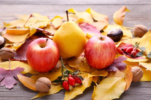 Folhas de outono com frutas e legumes na mesa cinza