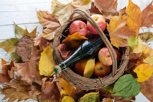 Folhas de outono com garrafa de cidra e maçãs na cesta