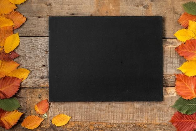 Folhas de outono com um quadro-negro em uma mesa de madeira