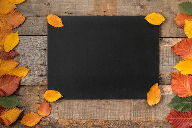 Folhas de outono com uma lousa em uma mesa de madeira