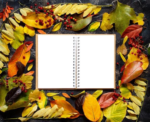 Folhas de outono e caderno em um fundo escuro