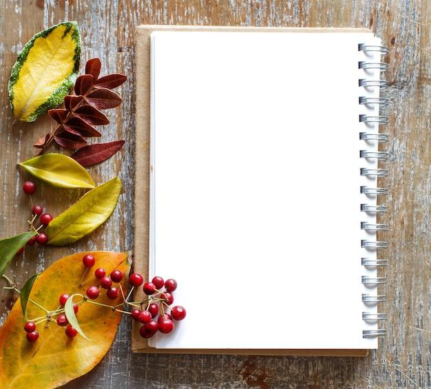 Folhas de outono e caderno em uma mesa de madeira