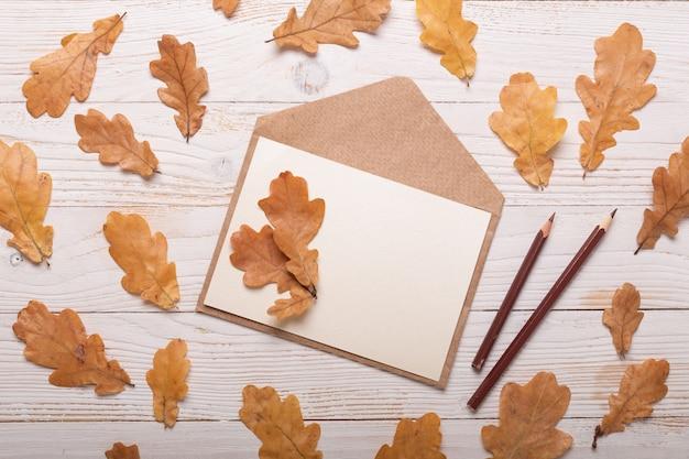 Folhas de outono e envelope em uma mesa de madeira branca