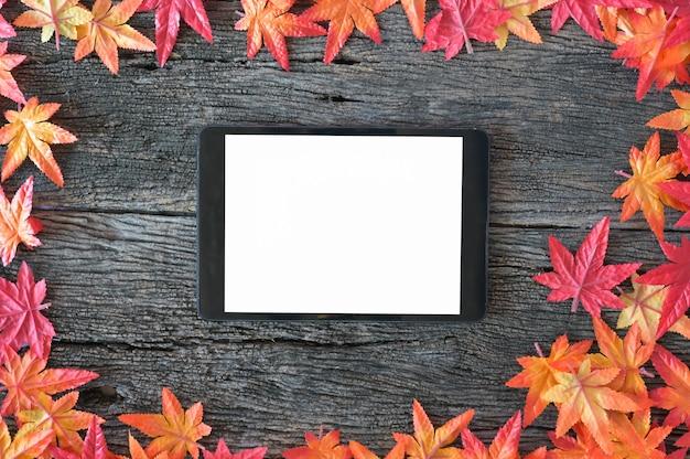 Folhas de outono e tabuleta digital do modelo no fundo de madeira da natureza com espaço da cópia.