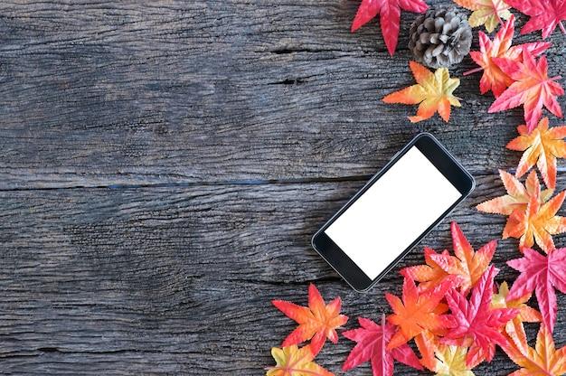 Folhas de outono e telefone celular do modelo no fundo de madeira da natureza com espaço da cópia.