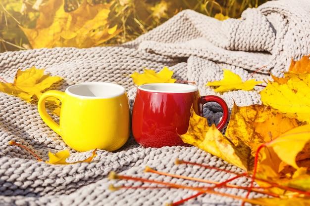 Folhas de outono e xícara de café fumegante quente.