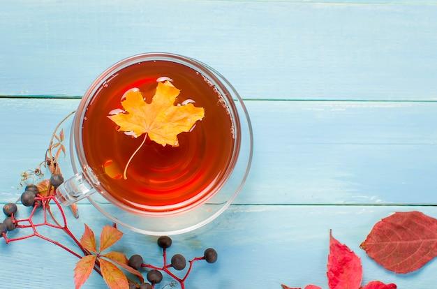 Folhas de outono e xícara de chá na mesa de madeira