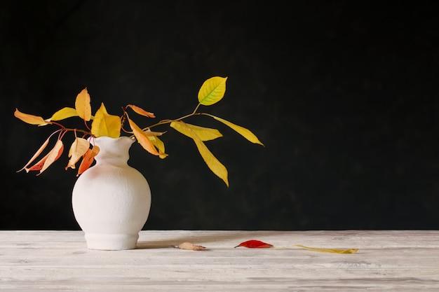 Folhas de outono em um vaso branco na mesa de madeira em fundo escuro