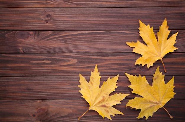 Folhas de outono laranja na mesa marrom. dia de ação de graças