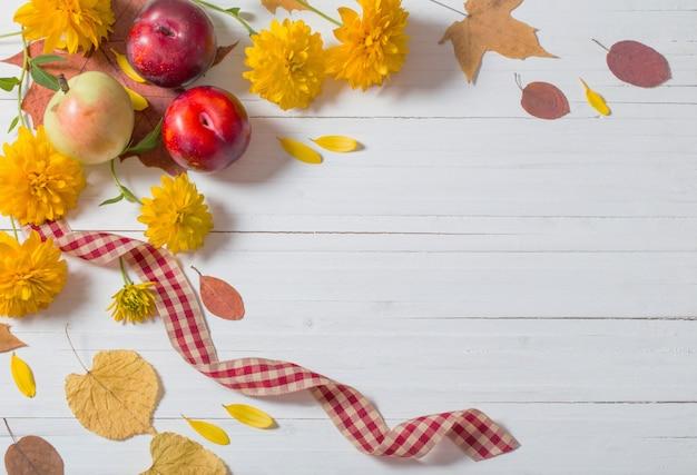 Folhas de outono na parede de madeira branca