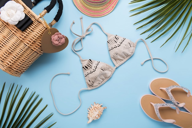 Folhas de palmeira, chapéu da moda, biquíni, chinelos, bolsa de praia de palha sobre uma superfície azul pastel clara, conceito de viagens e férias, vista superior
