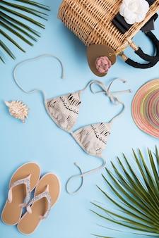 Folhas de palmeira, chapéu da moda, biquíni, chinelos, bolsa de praia palha sobre uma superfície azul pastel clara, conceito de viagens e férias
