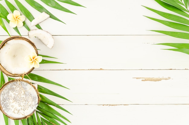 Folhas de palmeira com coco na mesa de madeira