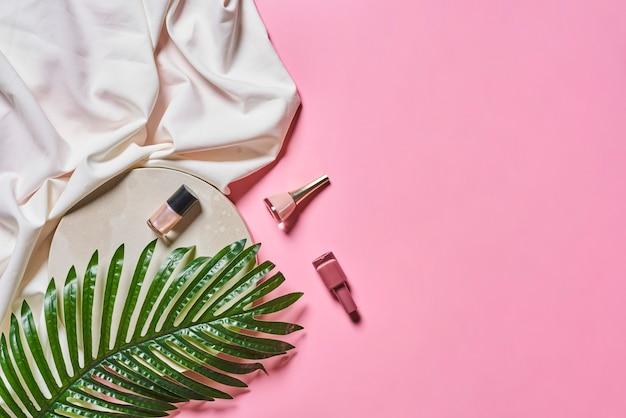 Folhas de palmeira de garrafas de esmalte em fundo rosa pastel com conceito de espaço de cópia