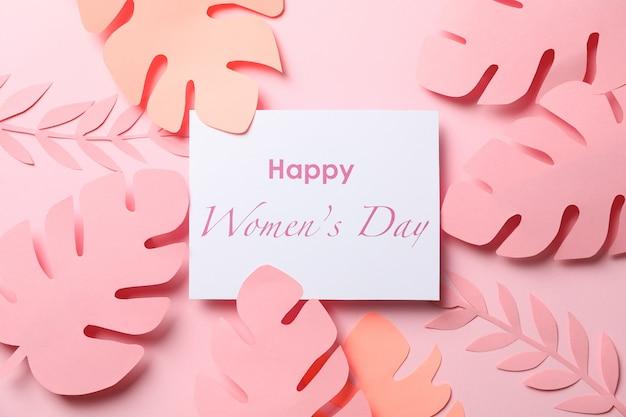 Folhas de palmeira decorativa e inscrição feliz dia da mulher na cor, vista superior