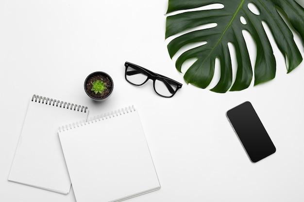 Folhas de palmeira e um caderno de papel com espaço livre para texto.