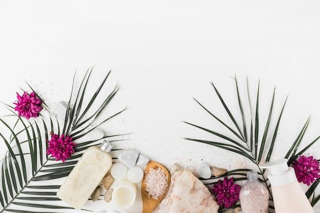 Folhas de palmeira; flor; esfoliação corporal; sal; pedras de spa em fundo branco