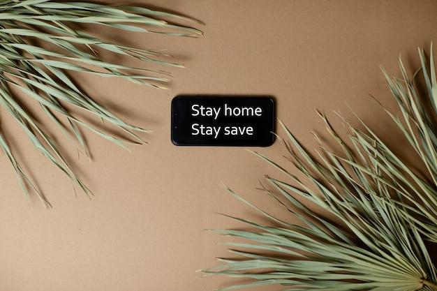 Folhas de palmeira secas em fundo de papel ofício. smartphone com ficar em casa ficar texto seguro.