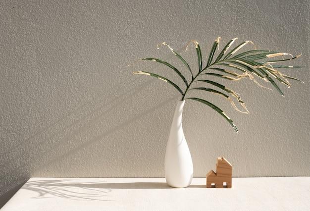 Folhas de palmeira secas em um lindo vaso de cerâmica branca e um modelo de casa na superfície da parede de cimento da mesa em tons de terra e espaço de cópia