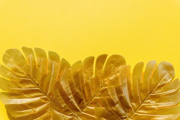 Folhas de palmeira tropical ouro monstera em fundo amarelo. verão exótico. período de férias. design brilhante e brilho, conceito de moda.
