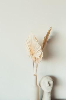Folhas de papel artesanal em leque bronzeado e busto na superfície branca