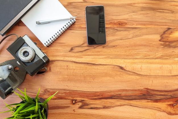 Folhas de papel, câmera retro e smartphone na mesa.